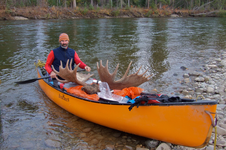 Brett in the canoe he paddled solo, with Igor's massive antlers sitting on top